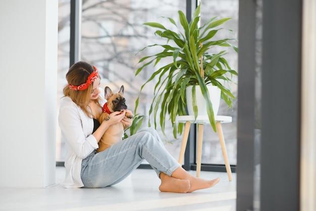 Wesoła młoda kobieta trzyma jej dużego szczeniaka z czarnym nosem i śmiejąc się. kryty portret uśmiechnięta dziewczyna pozuje z buldogiem francuskim