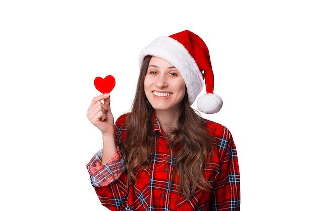 Wesoła młoda kobieta trzyma małe czerwone serce na znak dawania.