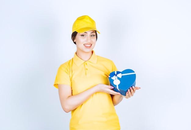 Wesoła młoda kobieta trzyma pudełko i patrzy na przód