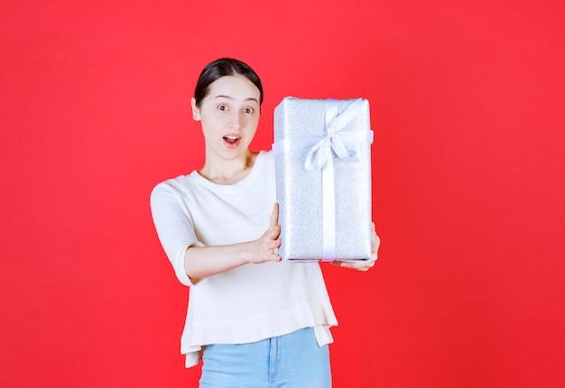 Wesoła młoda kobieta trzyma pudełko na prezent
