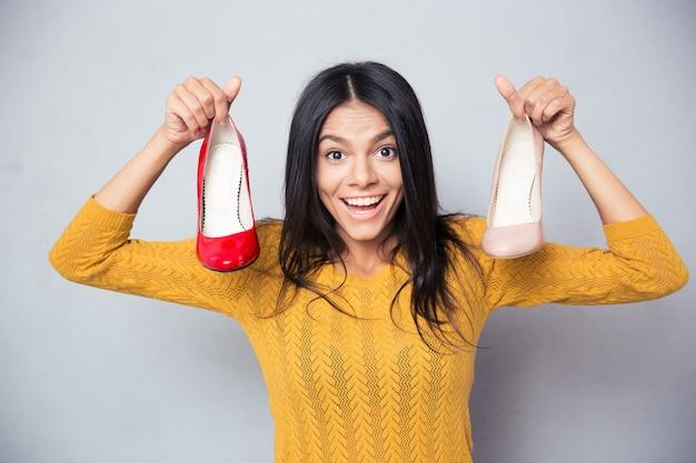 Wesoła młoda kobieta trzymając buty