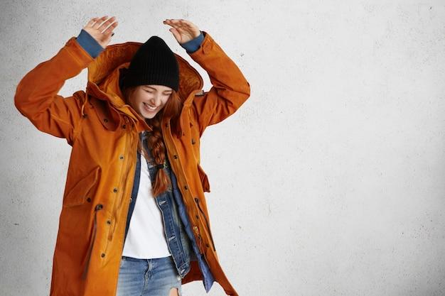 Wesoła młoda kobieta ubrana w rude włosy w warkocz, śmiejąca się głośno podczas zabawy w pomieszczeniu