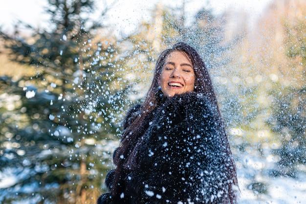 Wesoła młoda kobieta w ciepłym futrze, ciesząc się zimowym dniem w zaśnieżonym lesie