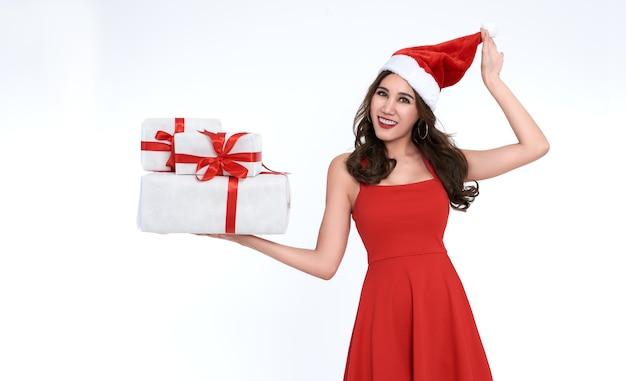 Wesoła młoda kobieta w czerwonej sukience santa gospodarstwa pudełko na boże narodzenie na białym tle.
