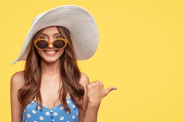 Wesoła młoda kobieta w kapeluszu pozuje na żółtej ścianie