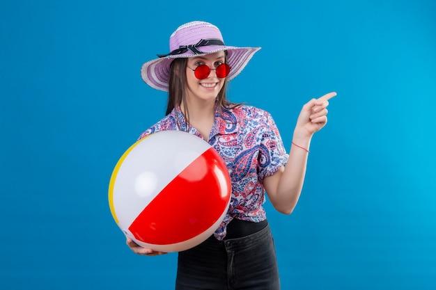Wesoła młoda kobieta w letnim kapeluszu w czerwonych okularach przeciwsłonecznych trzymająca nadmuchiwaną piłkę wskazującą palcem w bok, uśmiechnięta ze szczęśliwą twarzą stojącą nad niebieską przestrzenią