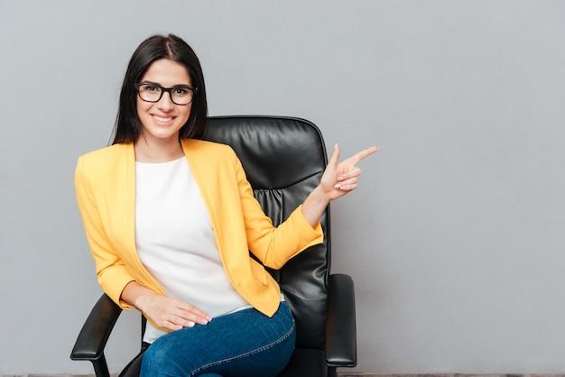 Wesoła młoda kobieta w okularach i ubrana w żółtą kurtkę, siedząc na krześle biurowym, wskazując na szarej powierzchni.