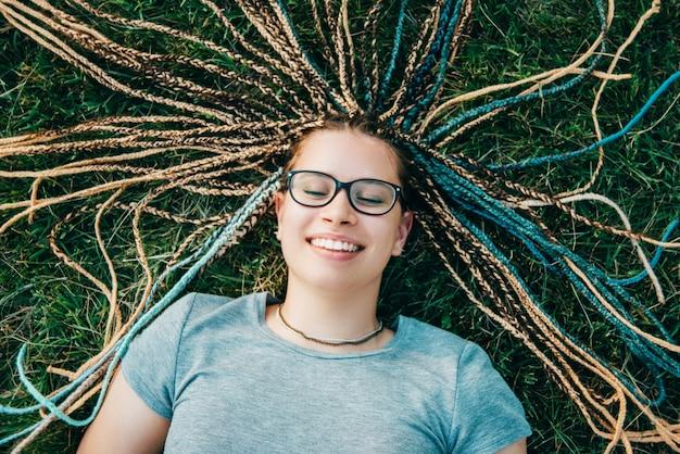 Wesoła młoda kobieta w okularach leży na trawie