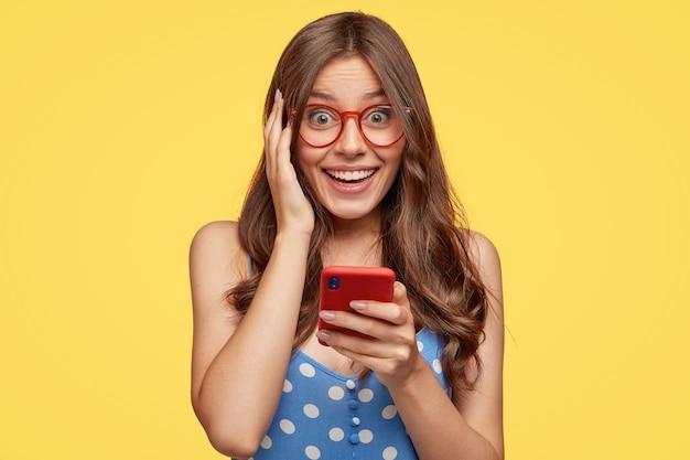 Wesoła młoda kobieta w okularach, pozowanie na żółtej ścianie