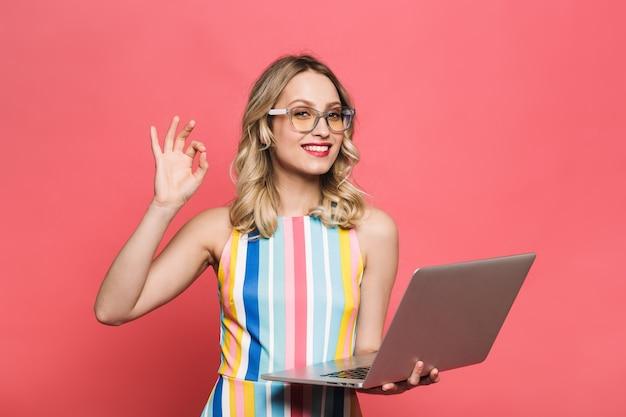 Wesoła młoda kobieta w okularach stojąca na białym tle nad czerwonym tłem