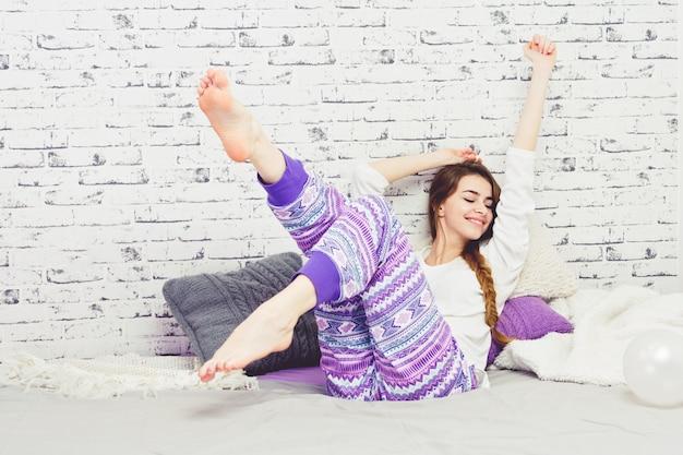 Wesoła młoda kobieta w piżamie, relaks w domu w łóżku