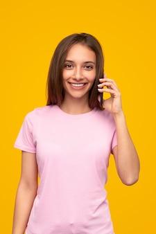 Wesoła młoda kobieta w różowej koszulce, uśmiechając się i patrząc, rozmawiając przez telefon komórkowy