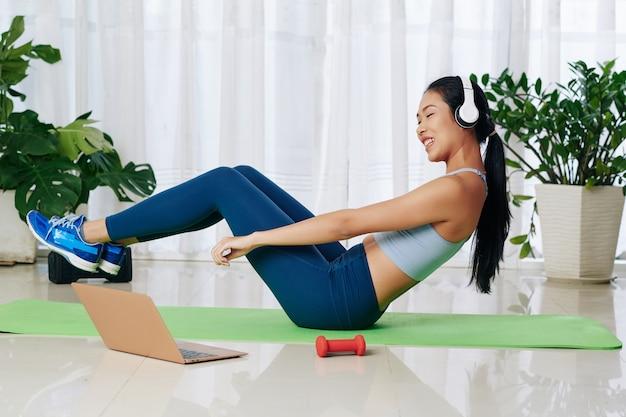Wesoła młoda kobieta w słuchawkach powtarza po trenerze online podczas wykonywania ćwiczeń abs