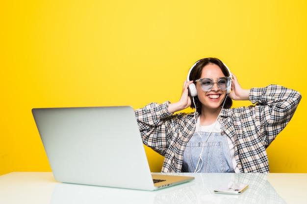 Wesoła młoda kobieta w słuchawkach tańczy do muzyki, siedząc przed komputerem