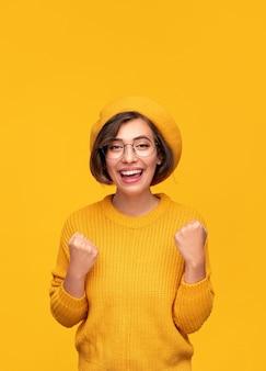 Wesoła młoda kobieta w stylowym swetrze i berecie, patrząc na kamerę z uśmiechem i zaciskając pięści, świętując zwycięstwo na żółtym tle