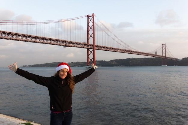 Wesoła młoda kobieta w świątecznym kapeluszu i z otwartymi ramionami o zachodzie słońca nad rzeką tag i mostem 25 kwietnia
