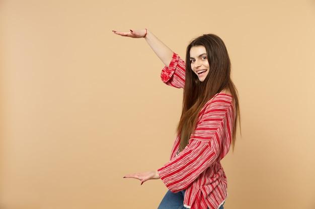 Wesoła młoda kobieta w ubraniach casual, wskazując rozmiar z pionowym obszarem roboczym na białym tle na tle pastelowej beżowej ściany. ludzie szczere emocje, koncepcja stylu życia. makieta miejsca na kopię.