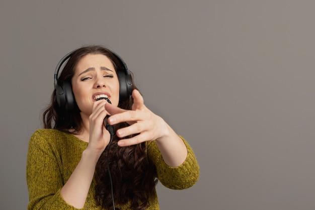 Wesoła młoda kobieta w ubranie ze słuchawkami śpiewa piosenkę w mikrofonie, makieta miejsce