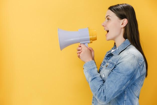 Wesoła młoda kobieta w wieku 20 lat krzycząca w megafonie