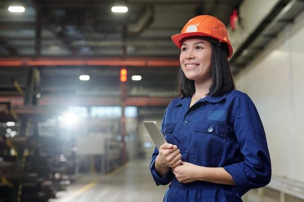 Wesoła młoda kobieta wngineer z touchpadem stojąca w warsztacie zakładu przemysłowego podczas kontroli procesu pracy