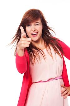 Wesoła młoda kobieta, wskazując na aparat