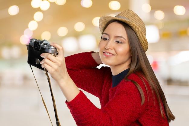 Wesoła młoda kobieta z aparatem
