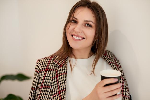 Wesoła młoda kobieta z gorącym napojem w kawiarni