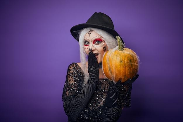 Wesoła młoda kobieta z halloweenowym makijażem i dynią