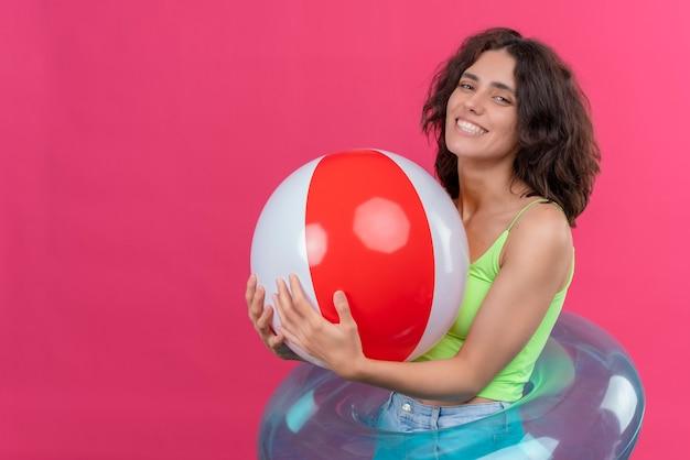 Wesoła młoda kobieta z krótkimi włosami w zielonej bluzce, uśmiechnięta i trzymająca nadmuchiwaną piłkę