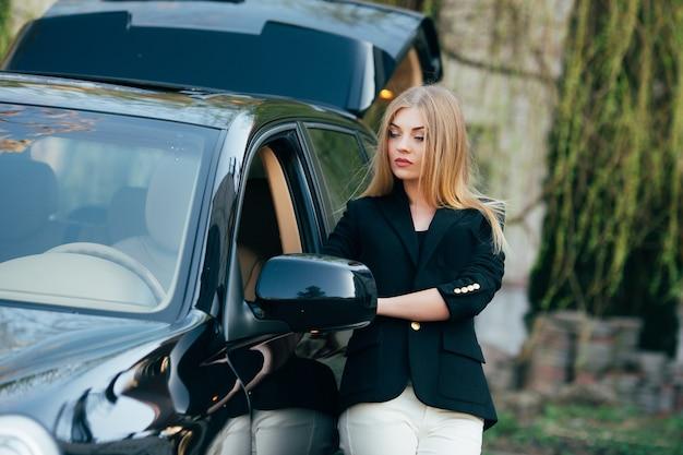 Wesoła młoda kobieta z luksusowym samochodem