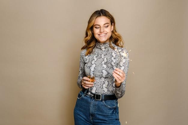 Wesoła młoda kobieta z płonącym brylantem, uśmiechając się przy lampce szampana z winem musującym na beżowym tle. boże narodzenie, nowy rok, koncepcja przyjęcia urodzinowego. skopiuj miejsce na tekst.