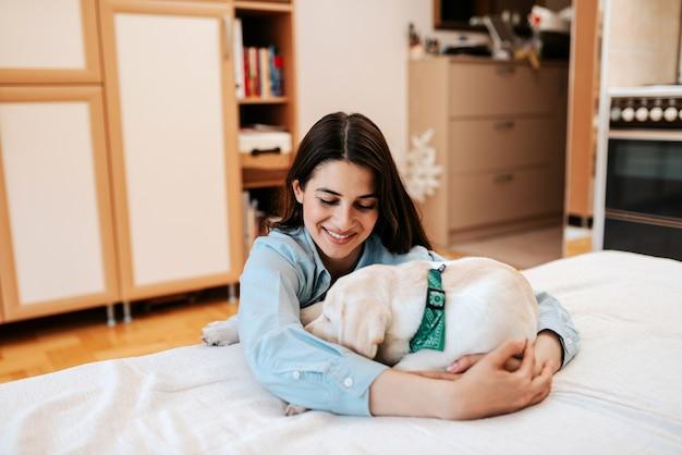 Wesoła młoda kobieta z psem w mieszkaniu.