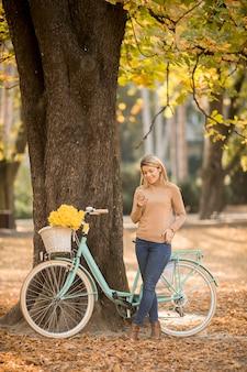 Wesoła młoda kobieta z rowerem za pomocą smartfona w jesiennym parku