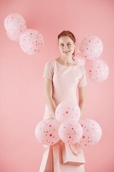Wesoła młoda kobieta z różowe balony i torby na zakupy