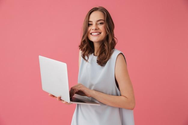 Wesoła młoda kobieta za pomocą laptopa