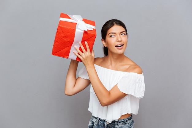 Wesoła młoda kobieta zastanawia się, co znajduje się w pudełku na prezent na szarej ścianie