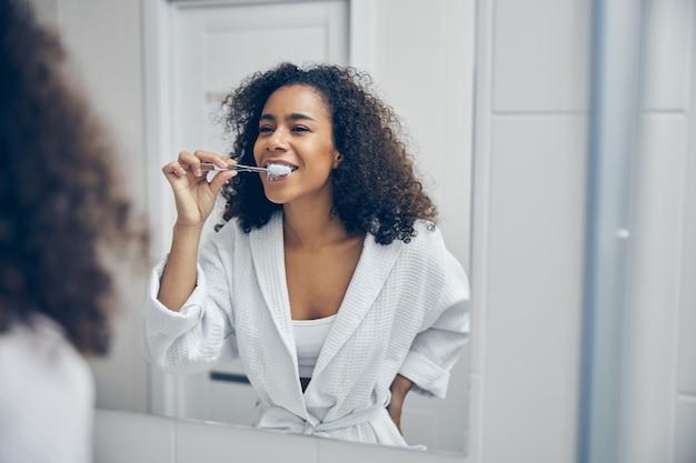 Wesoła młoda kobieta ze szczoteczką do zębów w ręku patrząca na siebie w lustrze