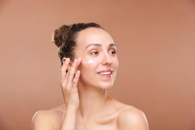 Wesoła młoda kobieta ze zdrowym uśmiechem patrząc na bok podczas nakładania kremu nawilżającego na strefę pod oczami podczas zabiegu kosmetycznego