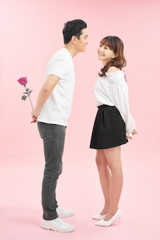 Wesoła młoda kochająca para trzyma różę i uśmiecha się, stojąc twarzą w twarz i izolowana na różowym tle