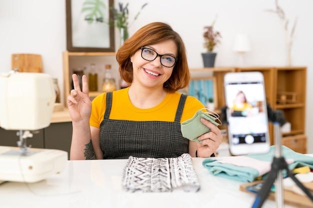 Wesoła młoda krawcowa w okularach siedzi przy biurku z tkaninami i trzyma maskę z tkaniny
