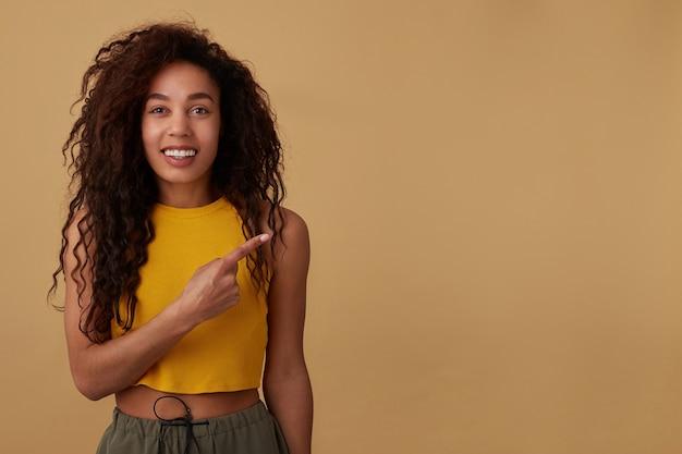 Wesoła, młoda, kręcona brunetka, ciemnoskóra kobieta wskazuje na bok palcem wskazującym i chętnie patrzy na aparat z szerokim uśmiechem, odizolowana na beżowym tle