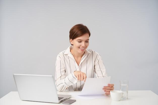 Wesoła młoda ładna brązowowłosa dama w formalnym ubraniu siedzi przy stole na białym tle, czytając tekst na kartce papieru i jest z niego zadowolona