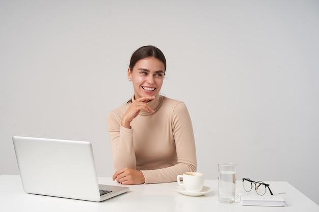 Wesoła młoda ładna brunetka kobieta uśmiecha się szeroko, patrząc na bok i opierając brodę na uniesionej dłoni, robiąc przerwę w pracy i pijąc filiżankę kawy, odizolowane na białej ścianie