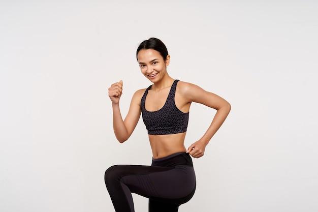 Wesoła młoda ładna ciemnowłosa kobieta ubrana w sportowy strój, radośnie uśmiecha się do przodu podczas wykonywania ćwiczeń fizycznych, odizolowane na białej ścianie