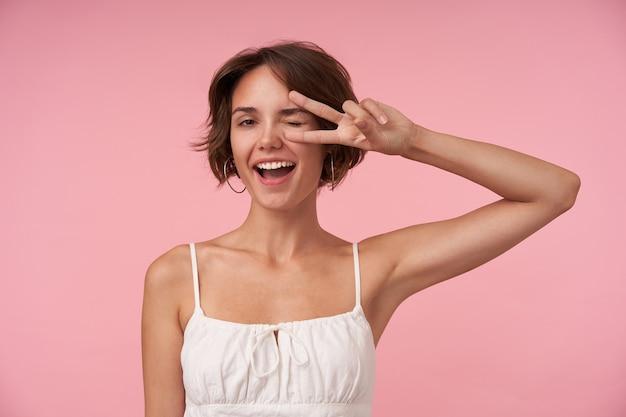 Wesoła młoda ładna dama z swobodną fryzurą ubrana w biały top podczas pozowania, patrząc radośnie z szeroko otwartymi ustami i podnoszącą rękę ze znakiem zwycięstwa