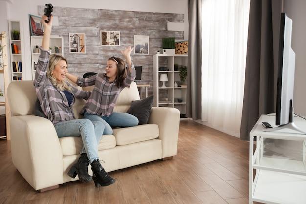 Wesoła młoda mama i jej córka o grach wideo. kontroler bezprzewodowy.