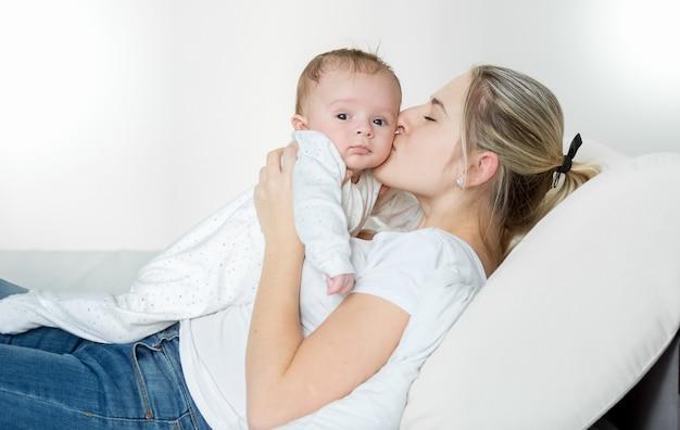 Wesoła młoda matka leży na łóżku i całuje swoje 3 miesięczne dziecko