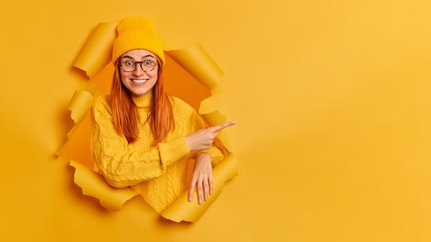 Wesoła młoda modelka ma rude włosy toothy uśmiech wskazujący na miejsce, ubrana w żółty sweter okularów skoczka.