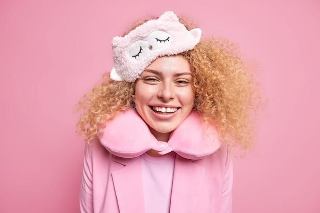Wesoła młoda modelka z kręconymi, krzaczastymi włosami uśmiecha się radośnie budzi się w dobrym nastroju, nosi maskę do spania i poduszkę pod szyję, aby wygodnie odpocząć, stoi szczęśliwa na tle różowej ściany. poranny czas