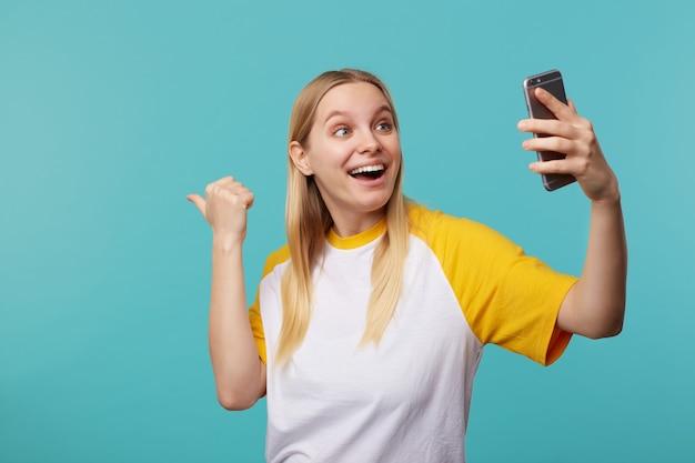 Wesoła młoda niebieskooka blondynka z przypadkową fryzurą, pokazująca podekscytowanie na bok podczas rozmowy wideo na smartfonie, stojąc na niebiesko